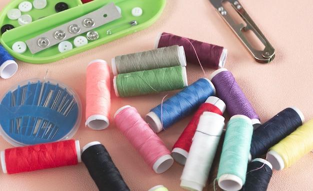 다채로운 실, 바늘 상자 및 단추는 배경에 파스텔을 넣습니다.