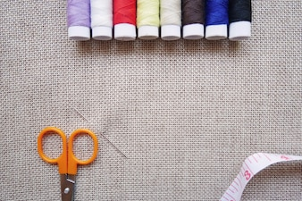 Colorful thread, scissors, measuring tape and pins on linen fabric
