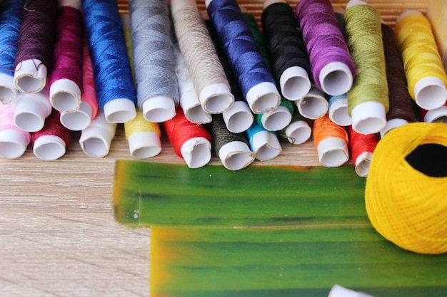 Colorful thread for sewing on wood background