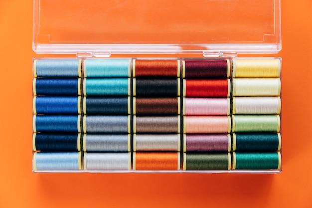 Разноцветные нитки в пластиковой коробке. оранжевый фон.
