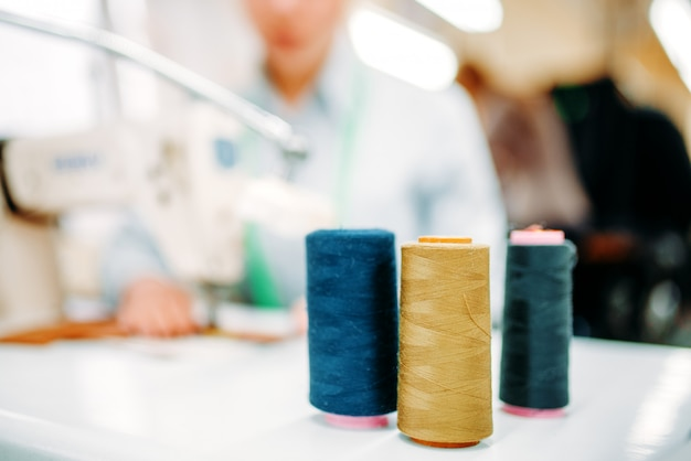 Colorful threads on spools closeup, dressmaking, sewing material, yarn on bobbins macro view, tailor on blur background