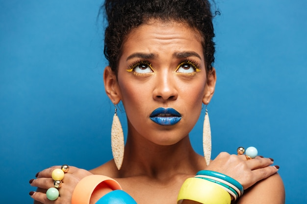Colorful thrilled mixed-race woman with trendy makeup and accessories looking upward with crossed hands on shoulders, over blue wall
