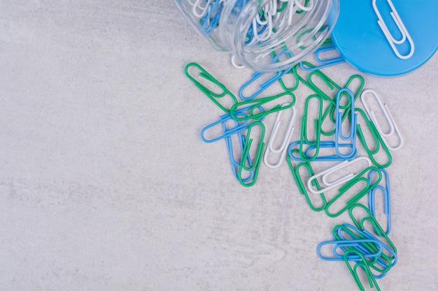 흰색 표면에 유리 항아리에 다채로운 압정