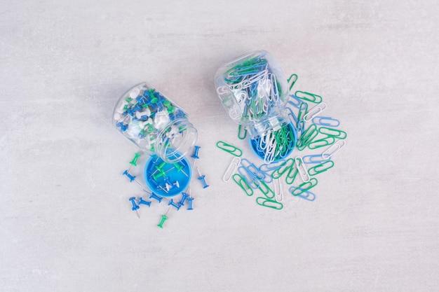 Puntine da disegno colorate in due barattoli di vetro sul tavolo bianco.