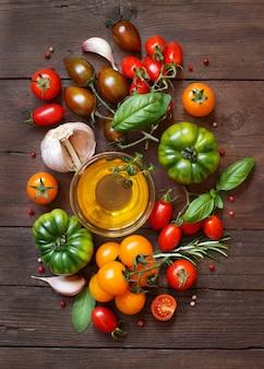 カラフルなトマト、ニンニク、オリーブオイル、ハーブを木製のテーブルに
