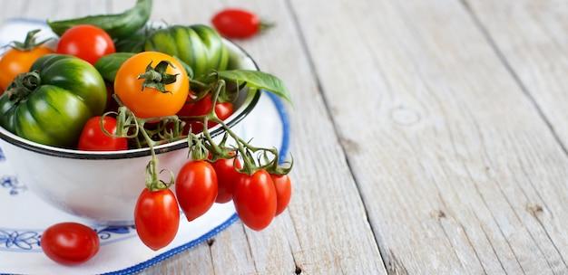 木製のテーブルの上のボウルにカラフルなトマト