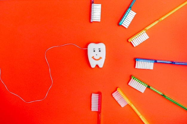Красочные зубные щетки arounf игрушка улыбающийся зуб. стоматологическая концепция.
