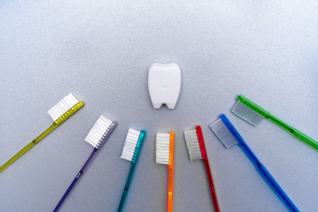 Colorful tooth brushes lay around tooth floss in tooth toy shape.