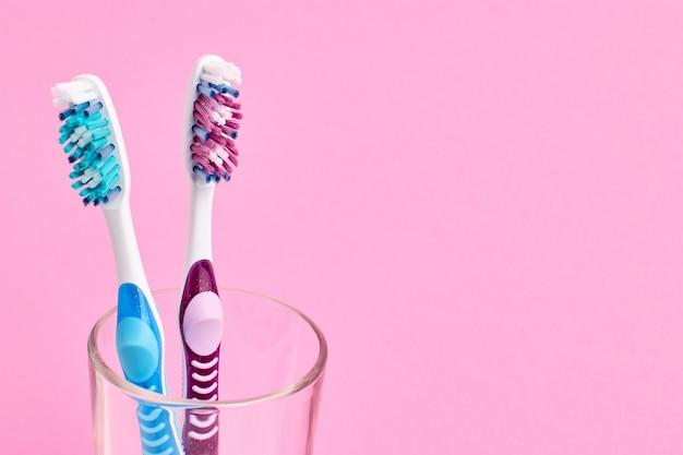 ガラスにカラフルな歯ブラシ。口腔衛生のコンセプトです。ピンクの背景。
