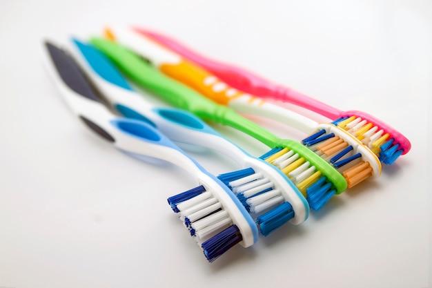 Красочные зубные щетки на белом фоне с копией пространства. макрос с мелкой степенями свободы.