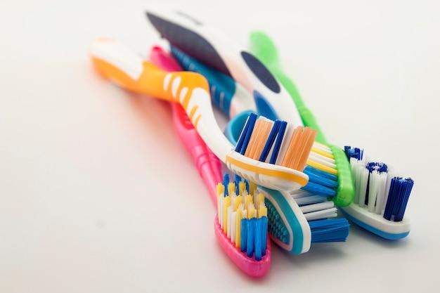 コピースペースと白い背景の上のカラフルな歯ブラシ。浅い自由度を持つマクロ。
