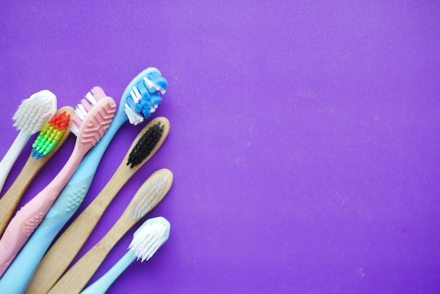 Colorful toothbrushes on purple background
