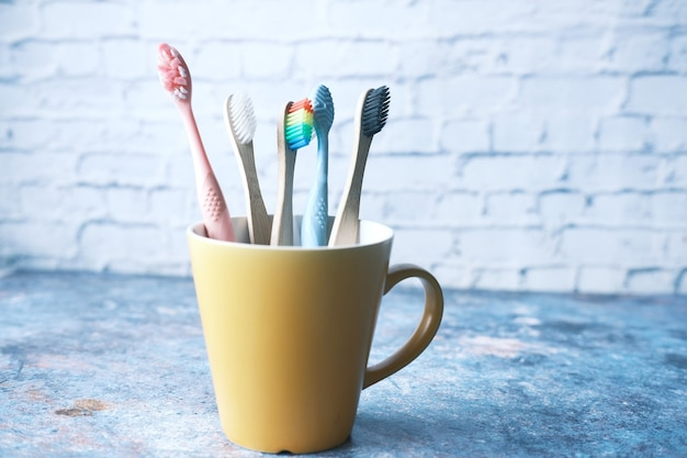 Colorful toothbrushes in white mug against a wall .