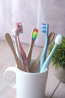 Colorful toothbrushes in white mug against a wall