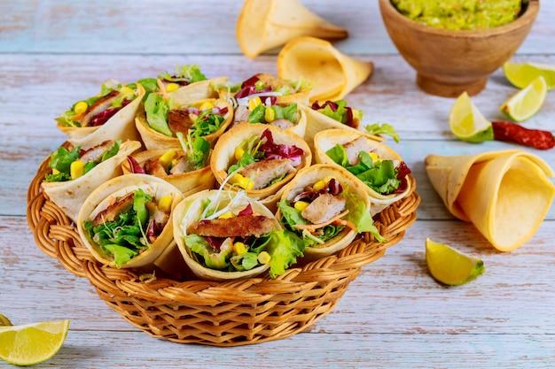 Colorful tortilla cones stuffed with fajita in wicker basket