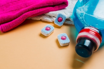 Colorful towels and liquid detergent with dishwasher tablets