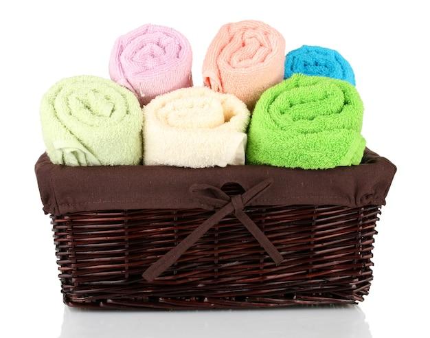 Красочные полотенца в корзине, изолированные на белом фоне