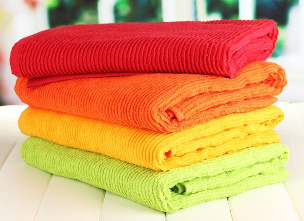 Colorful towels on wooden table on window