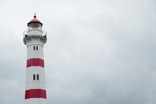 Colorful tower of lighthouse in overcast Free Photo