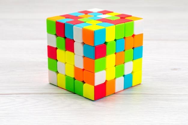 Costruzioni giocattolo colorate progettate e modellate su una scrivania leggera, cubo di rubiche in plastica giocattolo