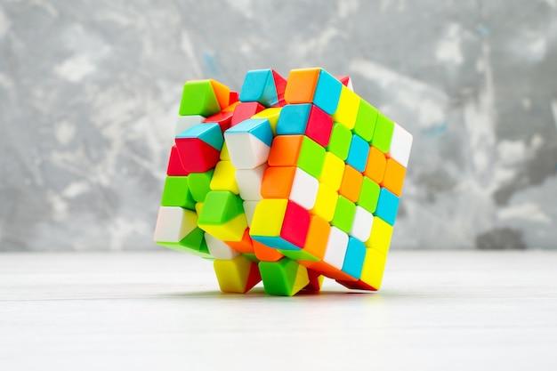 Costruzioni giocattolo colorate progettate e modellate sulla scrivania bianca, cubo di rubiche di costruzione in plastica giocattolo