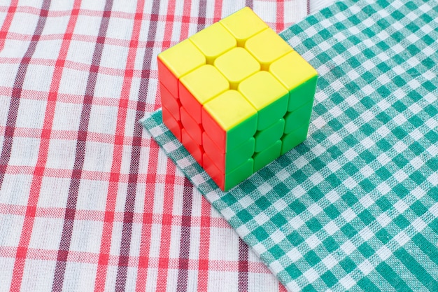 軽い机の上に形作られたカラフルなおもちゃの構造のルービックキューブ、おもちゃのプラスチック