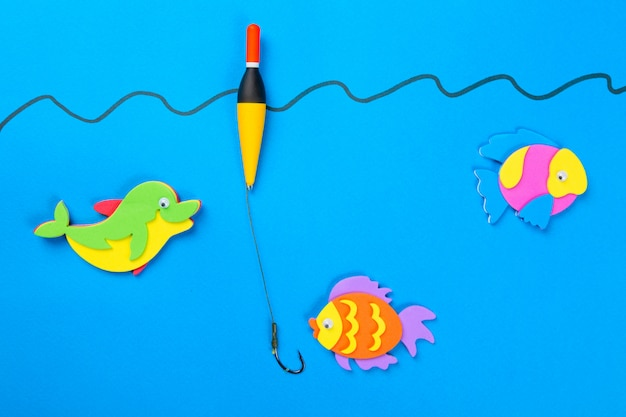 Colorful toy fish with a hook and fishing buoy on blue background.