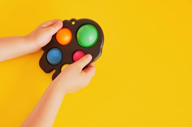 노란색 배경에 아이의 손에 다채로운 장난감 간단한 보조개