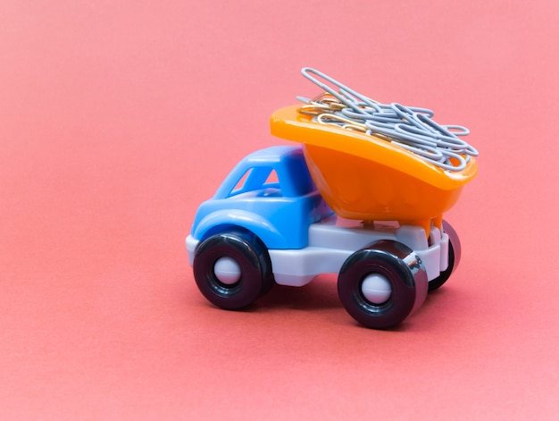 Colorful toy truck on a pink background, stationery in the back