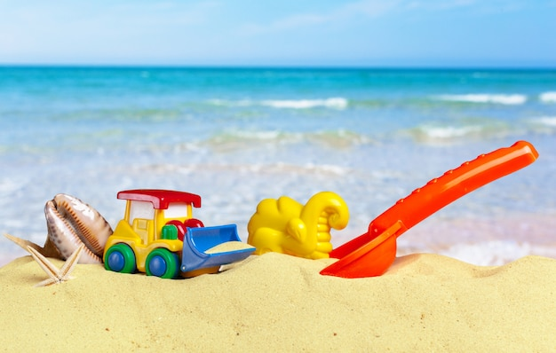 Colorful toys for child sandboxes against the beach sand background
