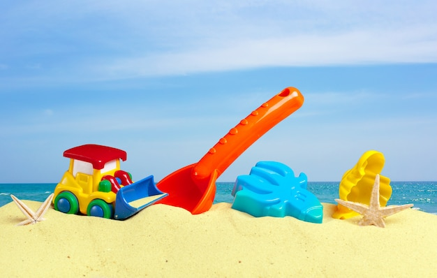 Colorful toys for child, sandboxes against the beach sand