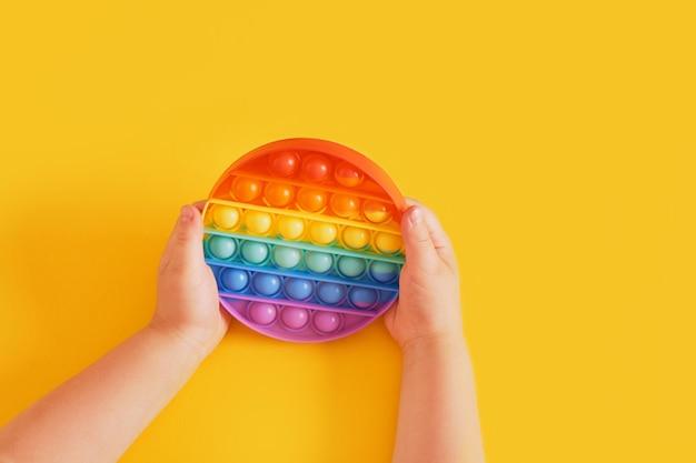 다채로운 장난감이 노란색 배경에 있는 어린이의 손에 팝니다