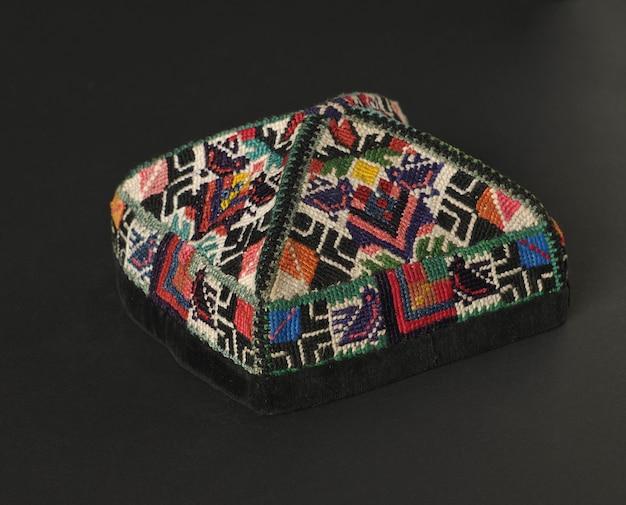 어두운 배경에 다채로운 전통 아시아 스컬 캡 모자