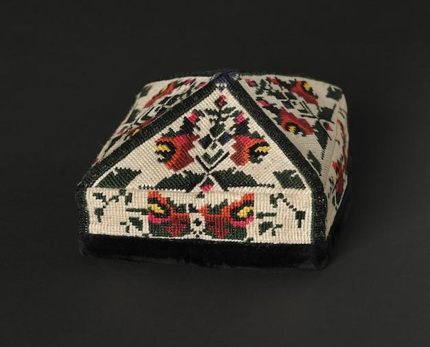 Красочная традиционная азиатская тюбетейка на темном фоне