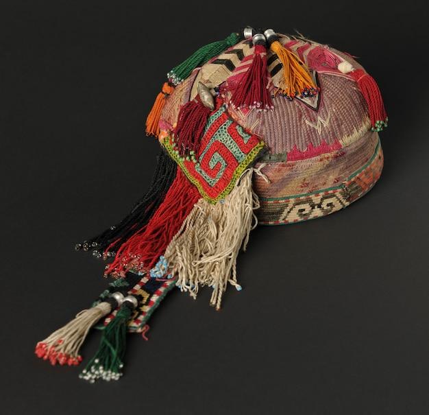 暗い背景にピグテールとカラフルな伝統的なアジアのスカルキャップ帽子