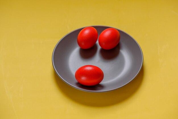 다채로운 전통 페인트 부활절 달걀입니다. 빨간 계란, 노란색 배경입니다. 노란색 배경에 회색 접시에 세 개의 계란. 색상 2021