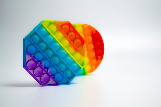 다채로운 트렌디한 스트레스 방지 감각 장난감 피젯 푸시 팝 및 파란색 배경에 간단한 보조개