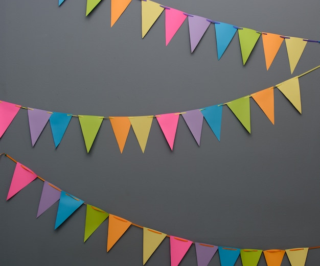 Colorful triangle diy party flags on a rope of a dark gray wall