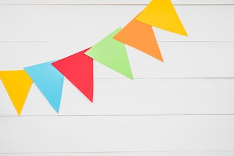 Colorful triangular bunting on white wooden plank