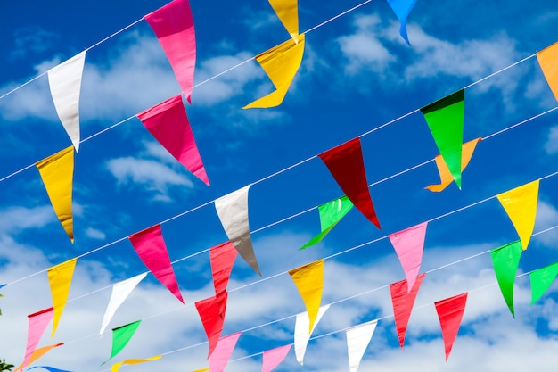 Colorful triangular flag line moving by wind on blue sky white cloud