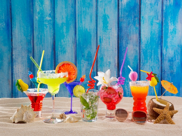 Colorful tropical cocktails at beach on blue wood wall