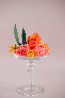 Colorful tropical flowers composition on glass cake stand on pinks, trends composition