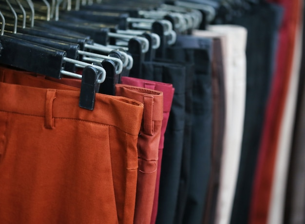 Colorful trousers with hanger on rack