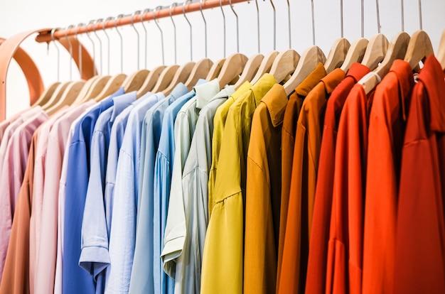 店内のハンガーからぶら下がっているカラフルなtシャツ