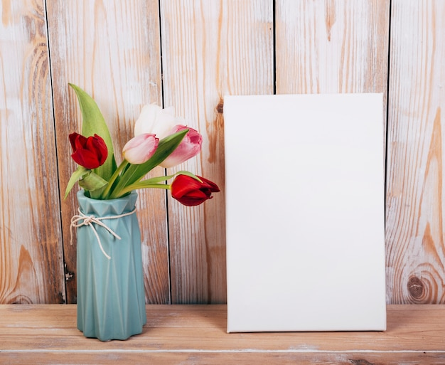 Colorful tulip flowers in vase with empty placard wooden backdrop