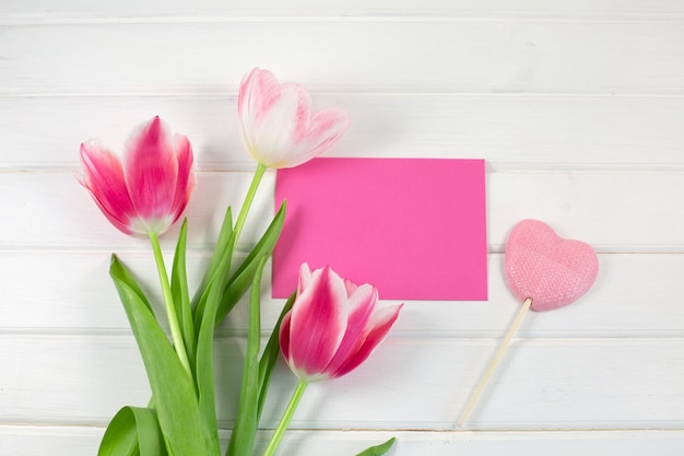 Красочные тюльпаны и печенье в форме сердца на белом деревянном столе. вид сверху с копией пространства.