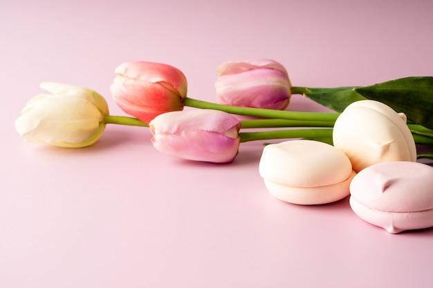 ピンクの背景にカラフルなチューリップやお菓子。お祝いの明るい春の背景。花とマシュマロの花束。 3月8日、誕生日、イースター、バレンタインデーのご挨拶。