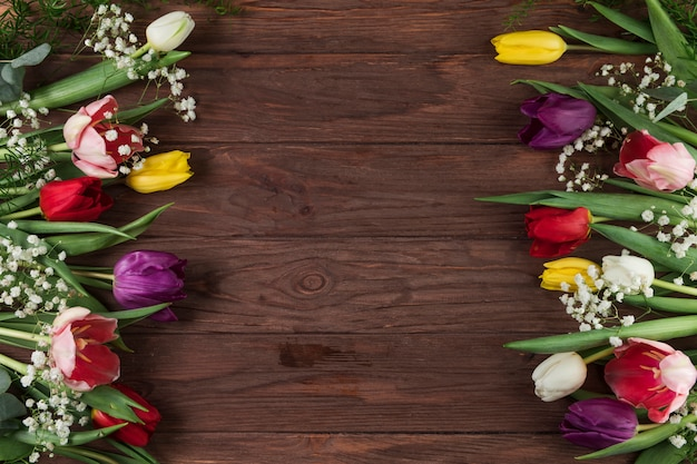 Colorful tulips and baby's breath flower on wooden textured table