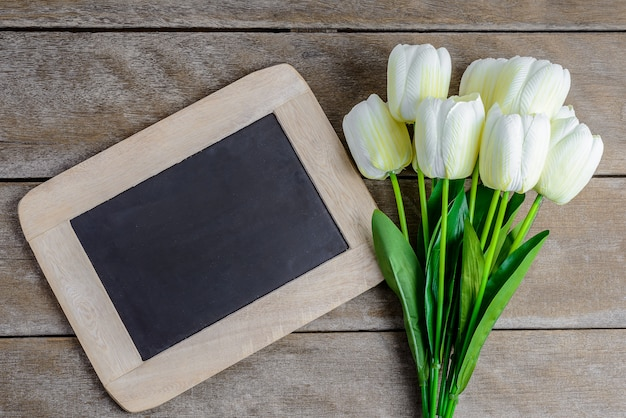 Colorful tulips bouquet and chalkboard on wooden background