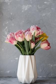 Красочные тюльпаны в белой вазе на столе